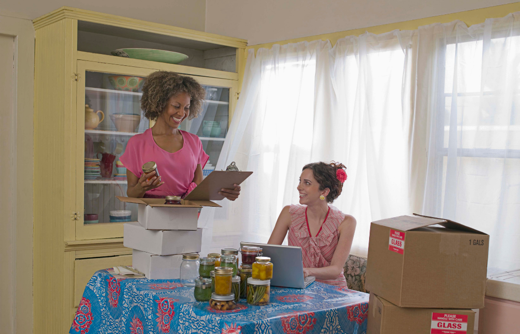 two female business women in aprons with jars of fruit in a bright kitchen