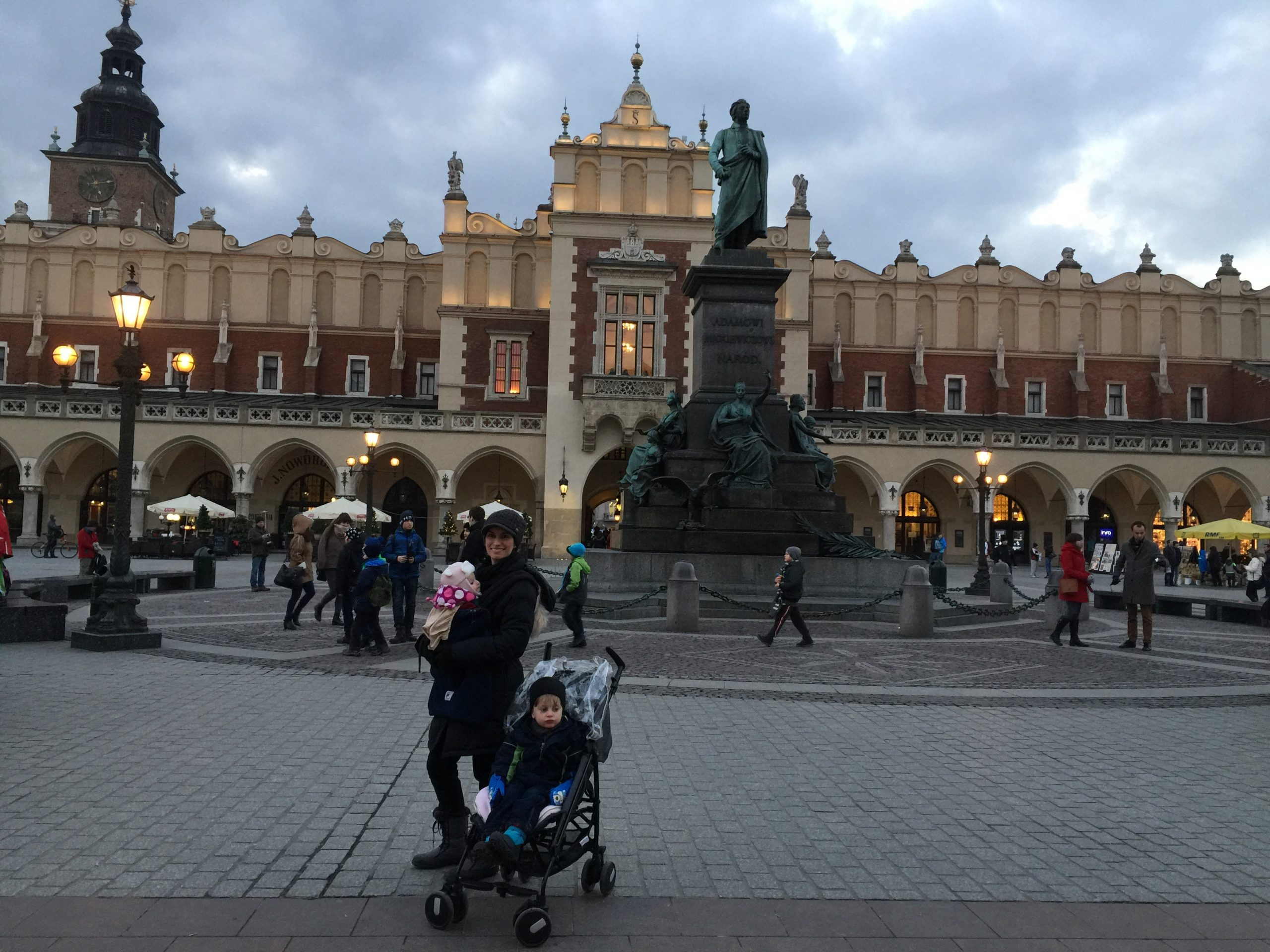Mother and children standing in the main square of Krakow, Poland 2016