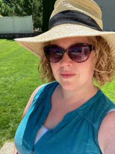 A white woman with curly hair stands in the sun. She is wearing sunglasses and a wicker hat.