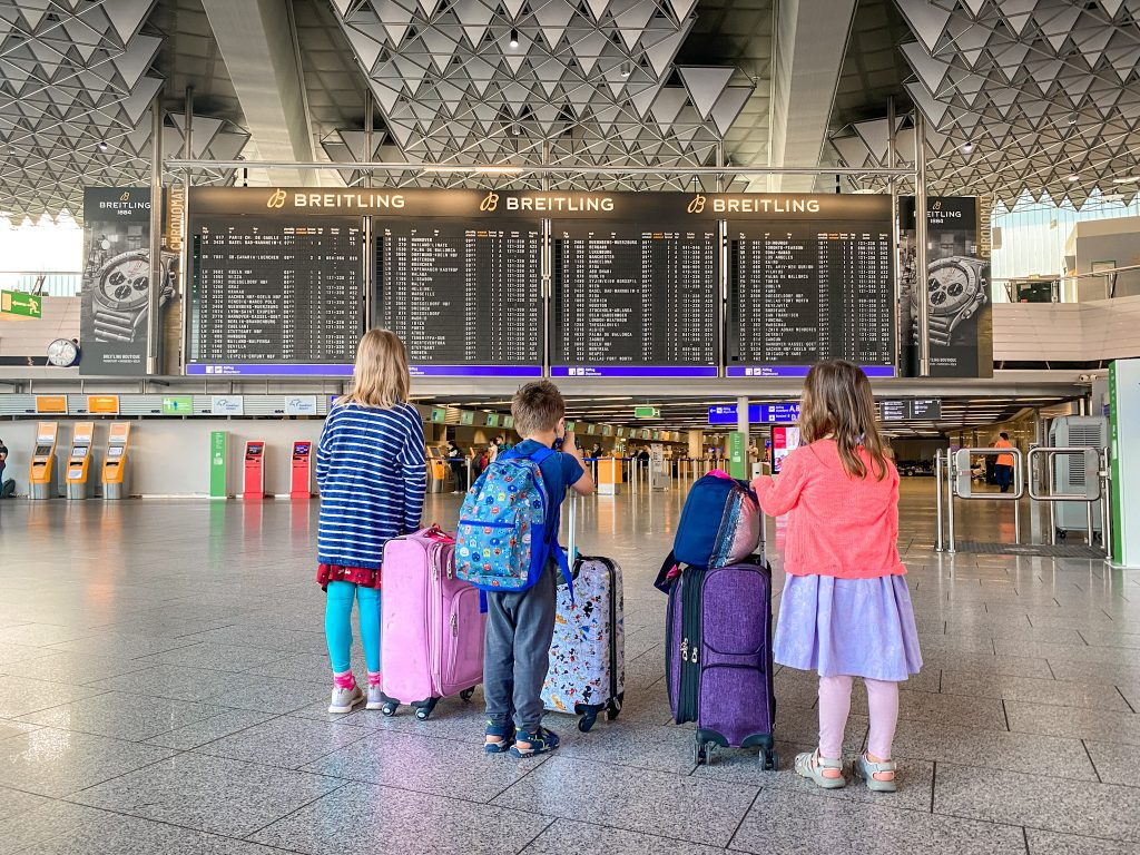 three children with suitcases in an airport