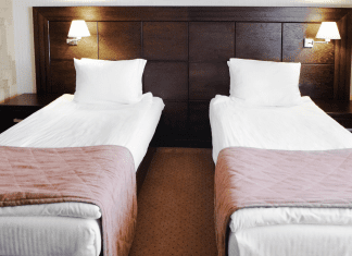 two beds in the same room with a dark wood headboard
