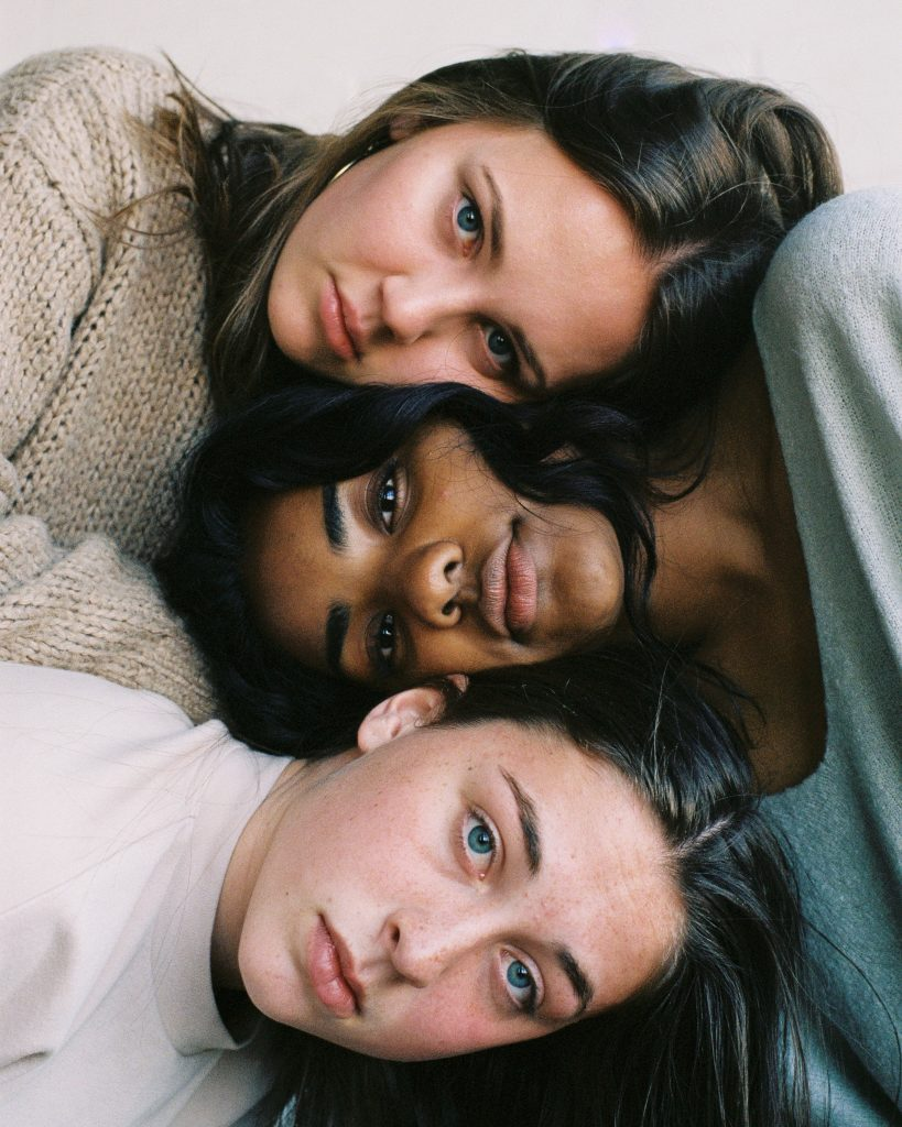 three women laying together