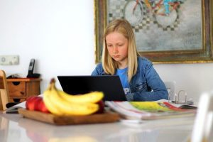 Girl sitting at a counter at home doing schoolwork