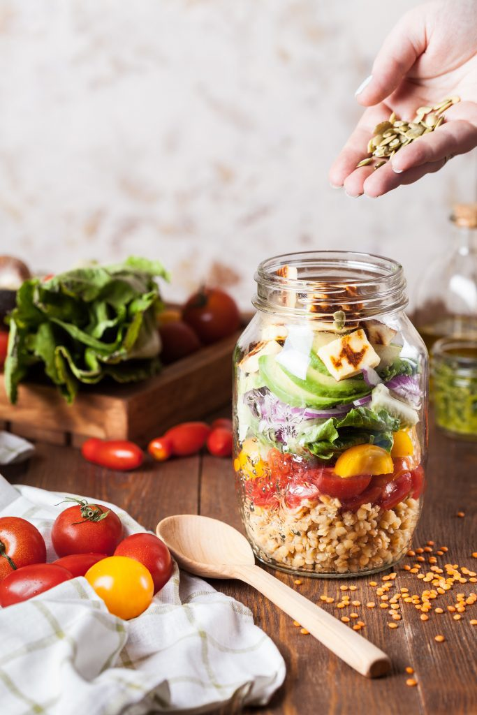 various vegetables on a cutting board with a spoon and jar for a salad in a jar meal