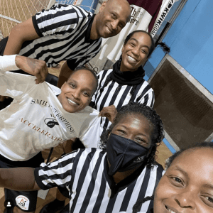 A group of five referees on the basketball court, 4 female, one male
