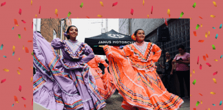 Hispanic dancers in traditional dress with a pale coral background and confetti