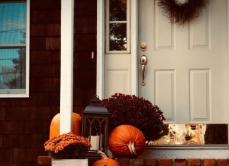 fall decor outside of a front door and porch