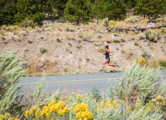 woman running on a road with dusty hillside in the background