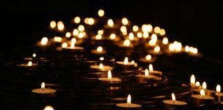 multiple lit votive candles to symbolize death or mourning