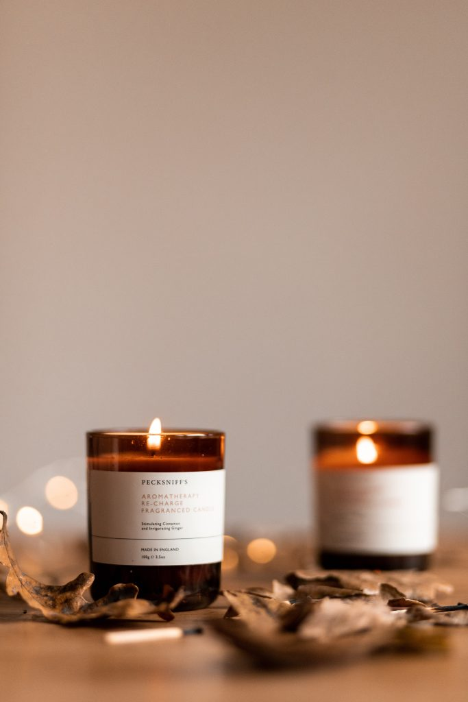 fall scented candles lit on a table with leaves