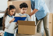children looking in a moving box with parent in background