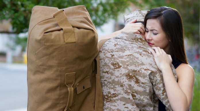 woman hugging a soldier with a military bag