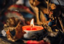 A lit orange tea light candle surrounded by fall leavess and