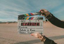 person holding a movie clapper in a desert scene