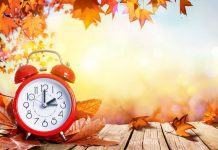 fall leaves and a sunny background with a red alarm clock
